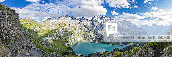 Aerial panoramic of Oeschinensee lake surrounded by woods in summer  Bernese Oberland  Kandersteg  Canton of Bern  Switzerland