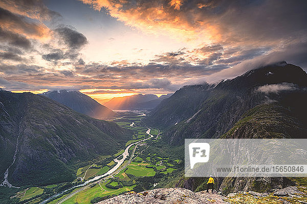 Elevated view of man standing on Romsdalseggen ridge admiring Rauma valley during sunset  Andalsnes  More og Romsdal  Norway  Scandinavia