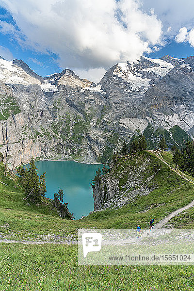 High angle view of two hikers walking on path above Oeschinensee lake,  Bernese Oberland,  Kandersteg,  Canton of Bern,  Switzerland