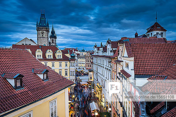 Heading to the Christmas Market in Prague's Old Town Square with the 600 year old Astronomical Clock standing tallest  UNESCO World Heritage Site  Prague  Czech Republic