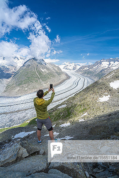 Rear view of man photographing Aletsch Glacier with smartphone from Eggishorn viewpoint  Bernese Alps  canton Valais  Switzerland