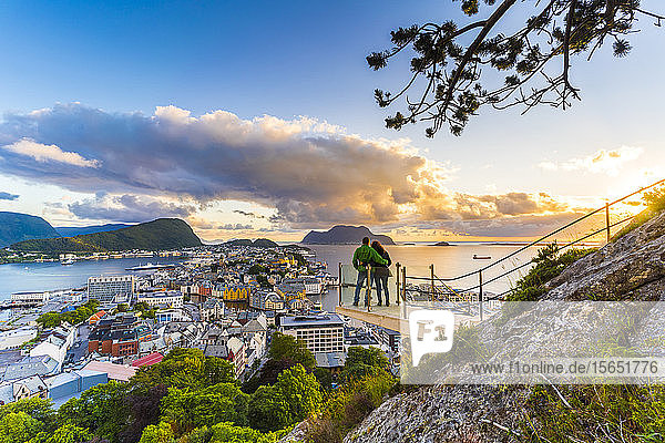 Couple embracing and enjoying the view of Alesund at sunset from Byrampen viewpoint  More og Romsdal county  Norway  Scandinavia