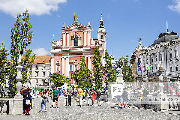 The Pink Franciscan Church in Preseren Square and tourists walking over the Triple Bridge  central Ljubljana  Slovenia  Europe