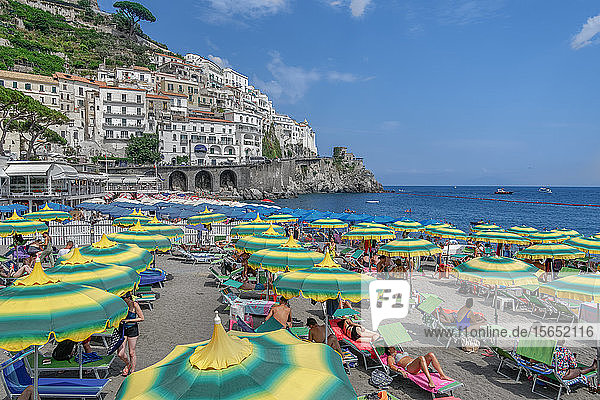 Beach view with bathers and colorful umbrellas before low rise buildings  Amalfi Town  Costiera Amalfitana  UNESCO World Heritage Site  Campania  Italy  Europe