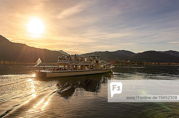 People traveling in ferry on Lake Tegernsee against sky during sunset  Bavaria  Germany