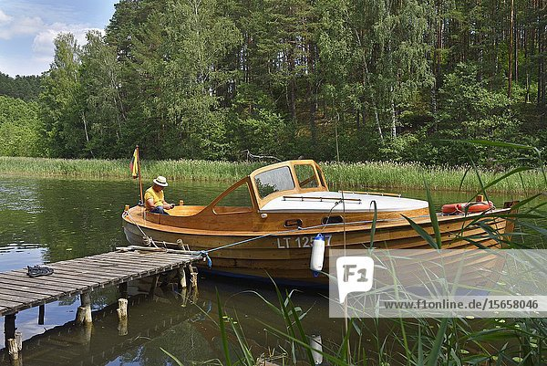Wooden motorboat trip along the lakes around Paluse  Aukstaitija National Park  Lithuania  Europe.