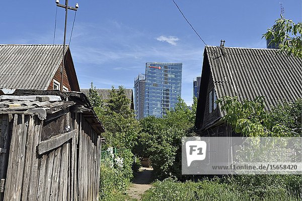 Old wooden houses surrounded by modern office towers in the Snipiskes district,  Vilnius,  Lithuania,  Europe.