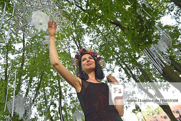 Young woman under movable geometrical constructions suspended in trees  Saint John Feast  Klaipeda  port city on the Baltic Sea  Lithuania  Europe.