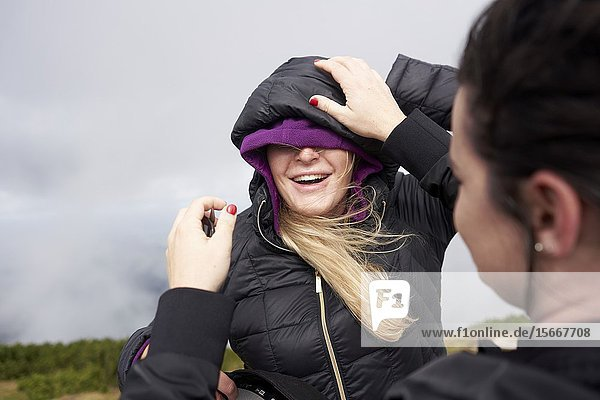 Friend helping happy woman with dressing warm clothes in cold stormy weather  hiking in mountains  Europe  Austria  Salzburg  Mount Untersberg.