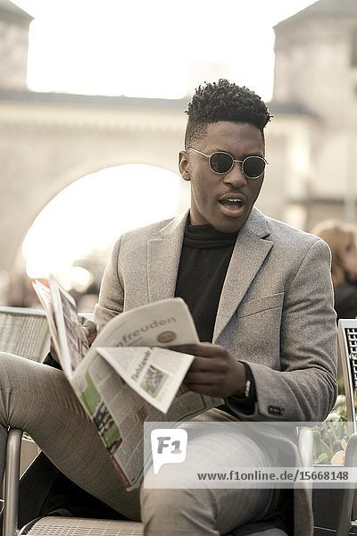 Young African man sitting on chair  reading newspaper  in Munich  Germany.