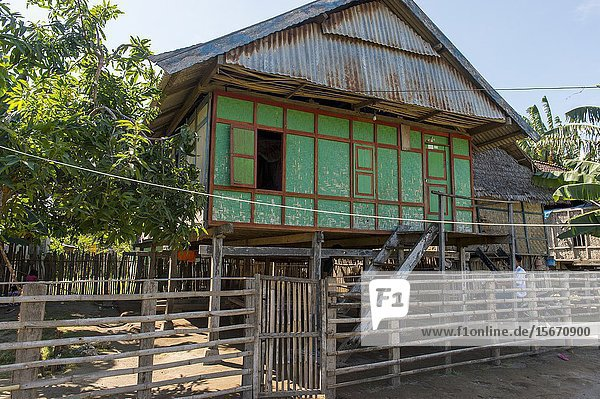 A village scene with a traditional house on stilts in the small village of Moyo Labuon on Moyo Island  off the coast of Sumbawa Island  Indonesia.