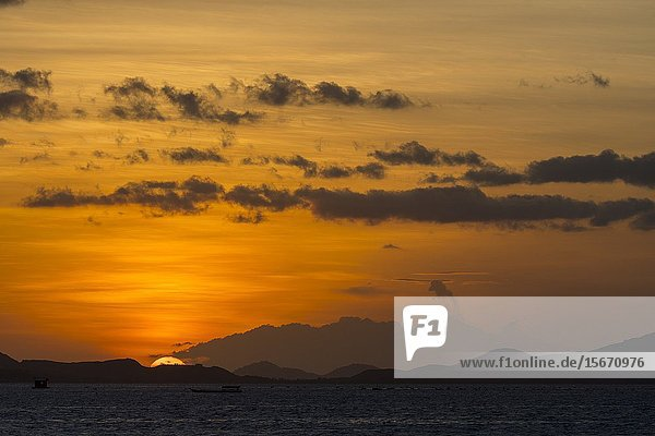 View from Kelor Island  a secluded island about 10 kilometers away from Labuan Bajo  Flores  and near Komodo Island  Komodo National Park in East Nusa Tenggara  Indonesia  of Sangeang Api Volcano erupting at sunset.