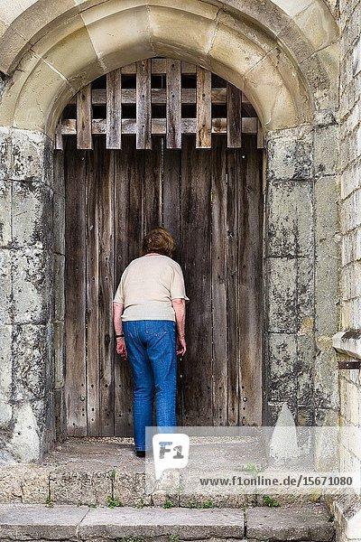 Nosey woman.looking through cracks in medieval door. Southampton City Walls England UK.