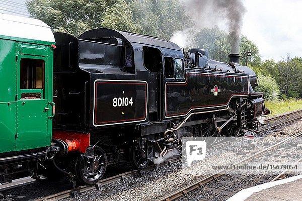 BR Standard class 4 tank engine 80104 steam train departing Corfe castle railway station Dorset UK.