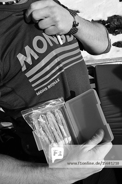 A snowboarder is showing a box full of joints for the highlight of his wintersport trip in the swiss alps.