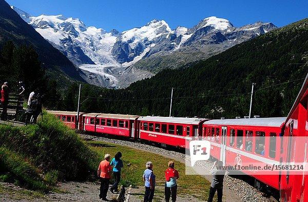 The Unesco world heritage Bernina train curving through the upper Engadin at Morteratsch glacier.