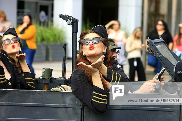 Forces entertainers wave and blow kisses to the people lining the streets of Tucson at the Veterans day parade.