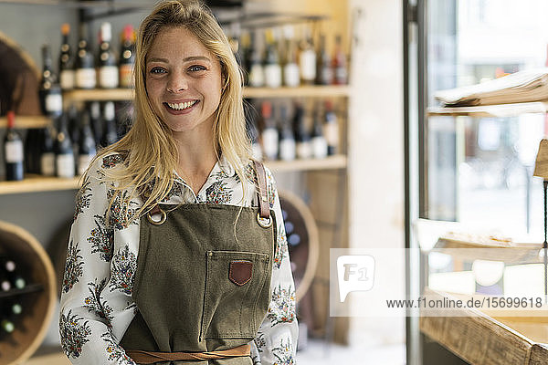 Smiling young woman standing in wine shop