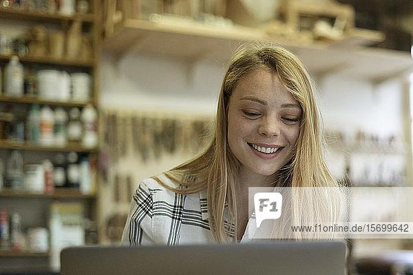Woman using laptop in workshop
