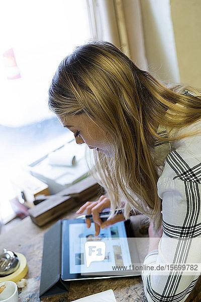 Woman using digital tablet in workshop