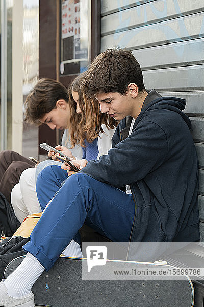 Friends using smartphone outdoors