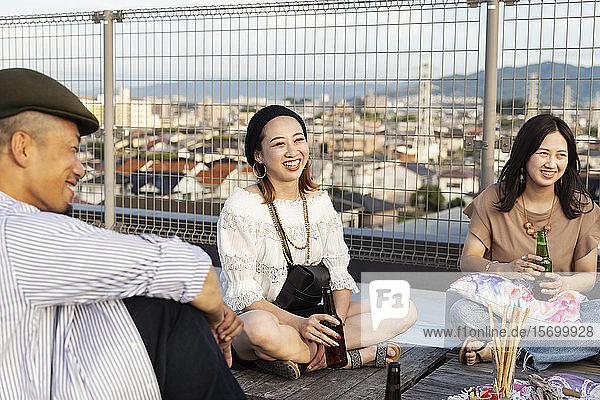 Lächelnde Gruppe junger japanischer Männer und Frauen  die auf einem Dach in einer städtischen Umgebung sitzen.