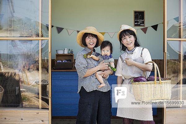Zwei Japanerinnen und ein Junge stehen vor einem Bauernladen und lächeln in die Kamera.
