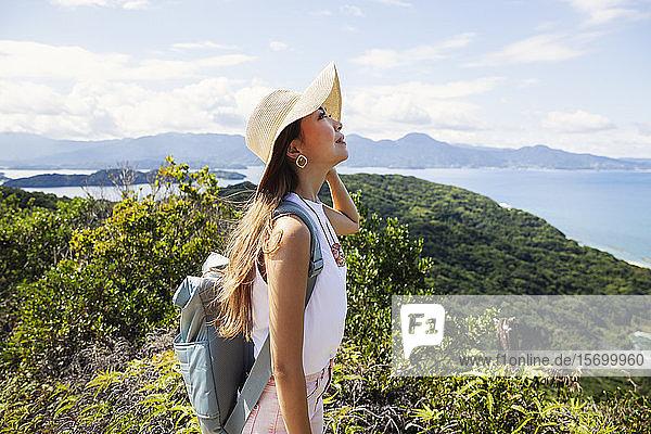 Japanische Frau mit Hut und Rucksack auf einer Klippe stehend  im Hintergrund das Meer.