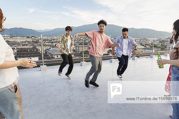 Gruppe junger japanischer Männer und Frauen  die auf einem Dach in einer städtischen Umgebung tanzen.