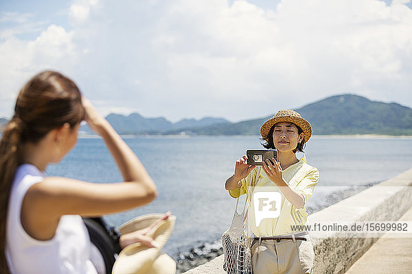 Zwei Japanerinnen stehen am Ozean und fotografieren mit dem Handy.