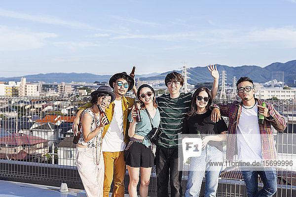 Gruppe junger japanischer Männer und Frauen  die auf einem Dach in einer städtischen Umgebung stehen.