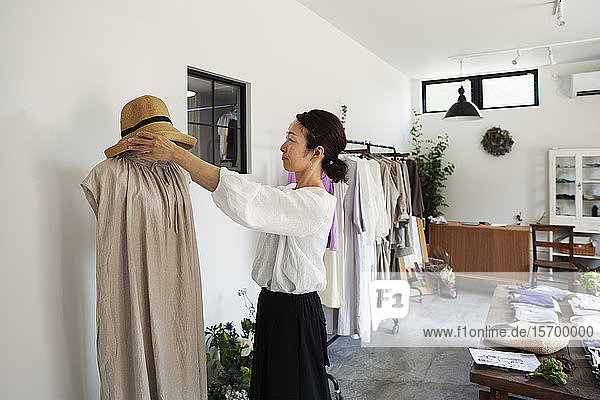 Japanese women standing in a small fashion boutique  arranging hat on mannequin.