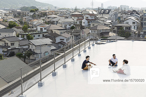 Hochwinkelansicht einer Gruppe junger japanischer Männer und Frauen  die auf einem Dach in einer städtischen Umgebung sitzen.