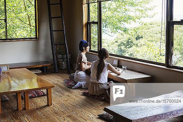 Zwei Japanerinnen sitzen an einem Tisch in einem japanischen Restaurant und essen.