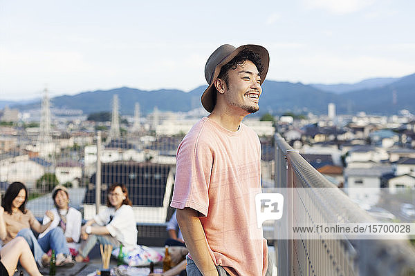 Lächelnder junger Japaner  der auf einem Dach in einer städtischen Umgebung steht.