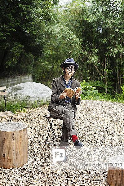 Japanerin mit Brille und Hut sitzt auf einem Stuhl vor dem Eco Cafe und liest ein Buch.
