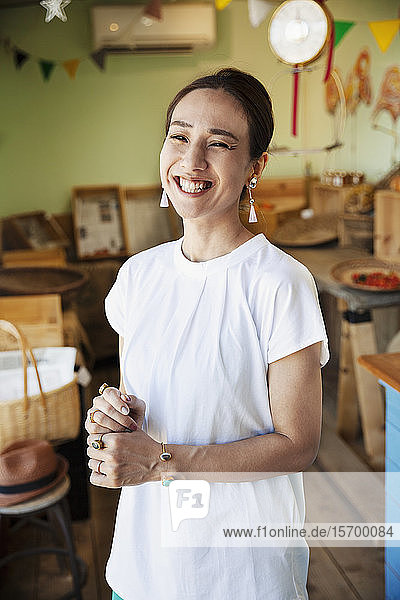 Smiling Japanese woman standing in a farm shop  looking at camera.