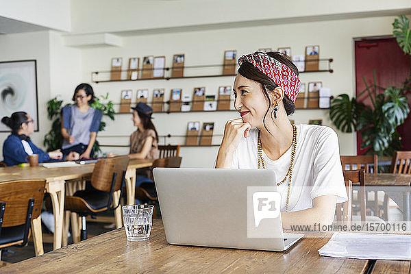 Gruppe junger japanischer Fachleute  die in einem Raum für Zusammenarbeit an Laptops arbeiten.