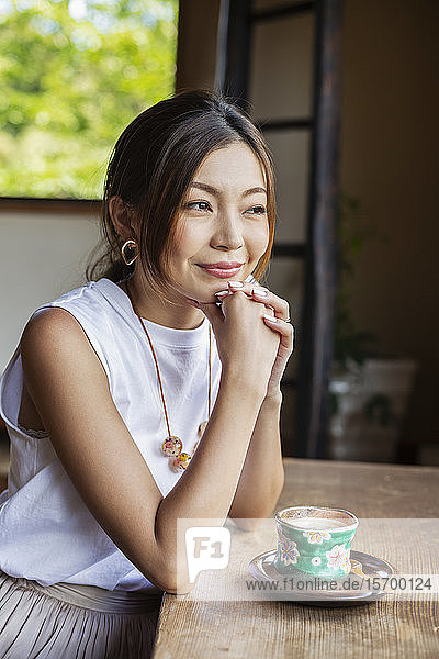 Smiling Japanese woman sitting at table in Japanese restaurant.