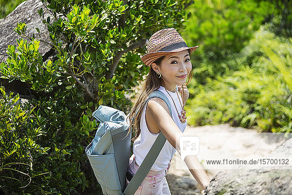 Japanese woman wearing hat and carrying backpack on a hike.