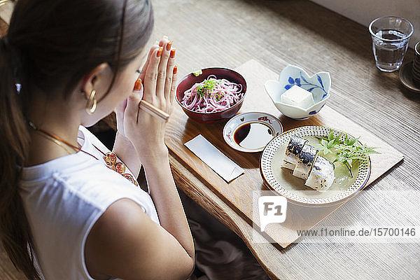 Schrägansicht einer Japanerin  die an einem Tisch in einem japanischen Restaurant sitzt und isst.