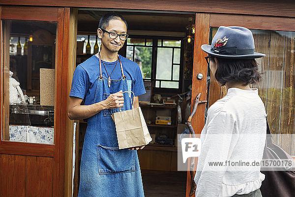 Japanische Frau und Mann mit blauer Schürze und Brille stehen vor einem Ledergeschäft und halten eine Einkaufstasche in der Hand.