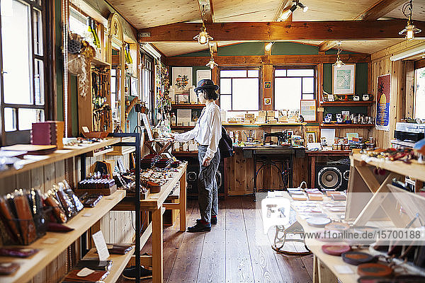Japanese woman browsing merchandise in a leather shop.