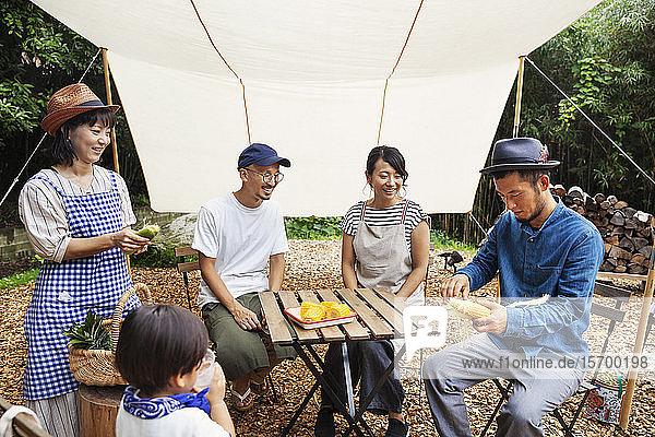 Eine Gruppe japanischer Männer und Frauen und ein Junge versammelten sich um einen Tisch unter einem Baldachin und bereiteten Gemüse zu.