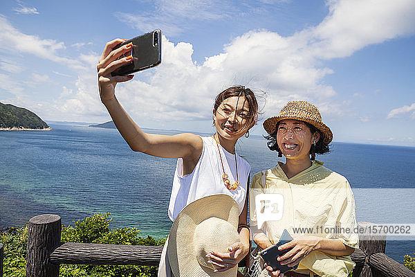 Zwei Japanerinnen mit Hüten auf einer Klippe stehend  Selfie mit Handy  im Hintergrund das Meer.