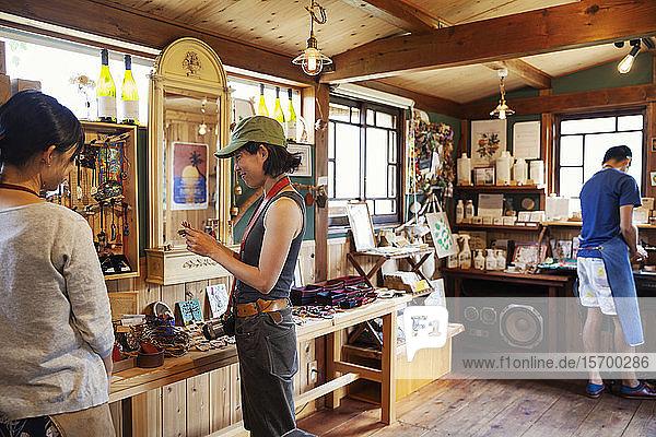 Zwei Japanerinnen und ein Japaner stehen in einem Ledergeschäft.
