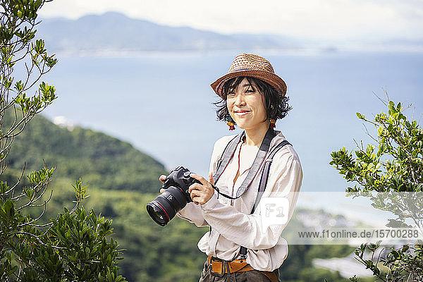 Japanerin mit Hut  Rucksack und Kamera auf einer Klippe stehend  im Hintergrund das Meer.