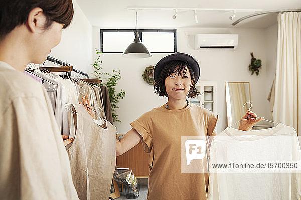 Zwei Japanerinnen stehen in einer kleinen Modeboutique und schauen auf Oberteile.