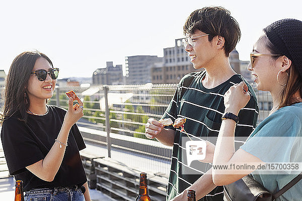 Young Japanese man and two women standing on a rooftop in an urban setting  drinking beer.