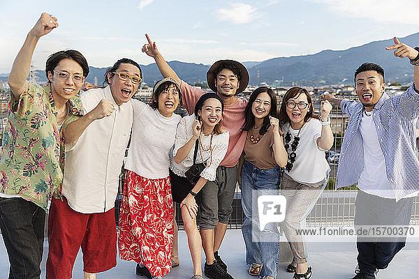Lächelnde Gruppe junger japanischer Männer und Frauen  die auf einem Dach in einer städtischen Umgebung stehen.